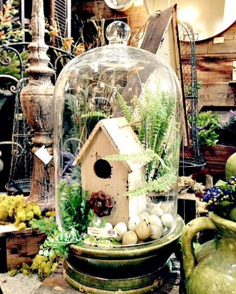 a cloche with a bird house, eggs and some greenery is perfect for spring