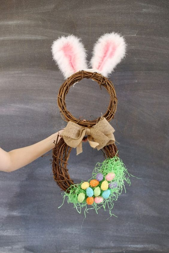 a grapevine bunny wreath with fluffy ears, a burlap bow and faux eggs
