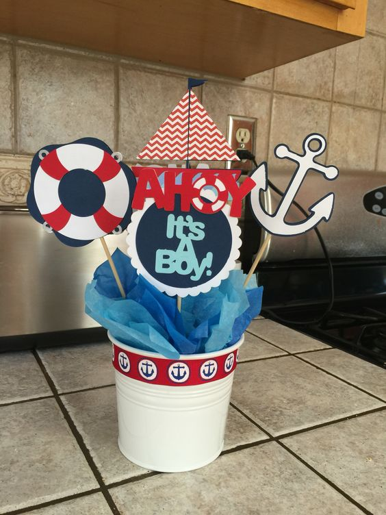 a nautical baby shower centerpiece with a paper anchor and a sail