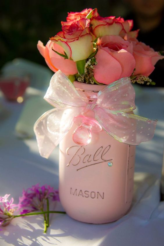 A Pink Mason Jar With A Ribbon Bow And Pink And Peachy Roses