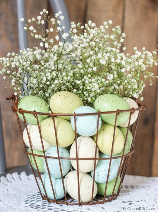 a wire basket with pastel eggs and baby's breath