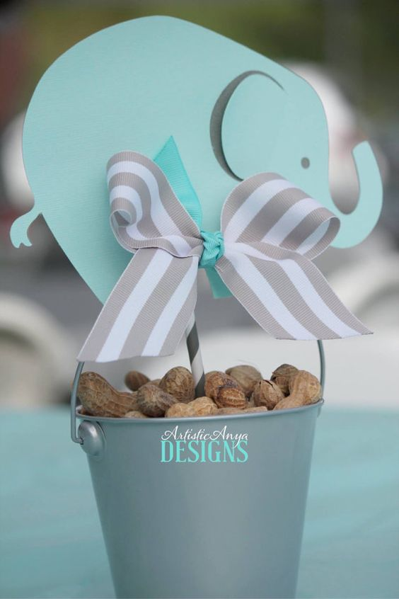 a peanut bucket with a paper elephant and a ribbon bow