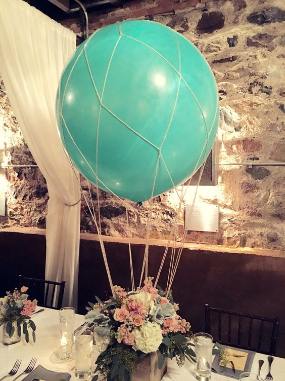a wooden box with a floral arrangement and a large balloon to make a hot air balloon look