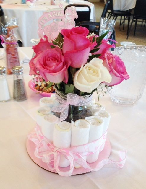 a diaper centerpiece with a vase and fresh pink roses