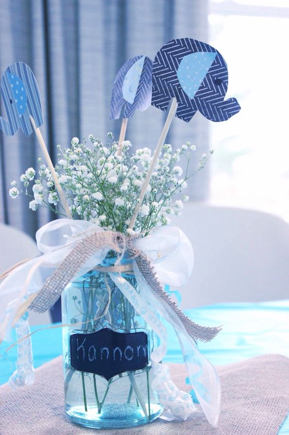 a mason jar, baby's breath, paper elephants, ribbon bows