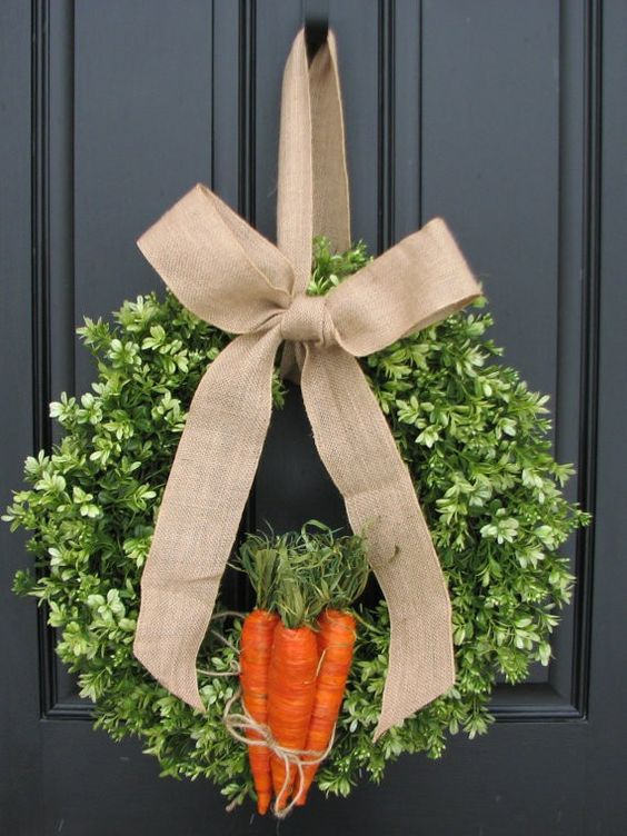 boxwood wreath with a burlap bow and faux carrots attached