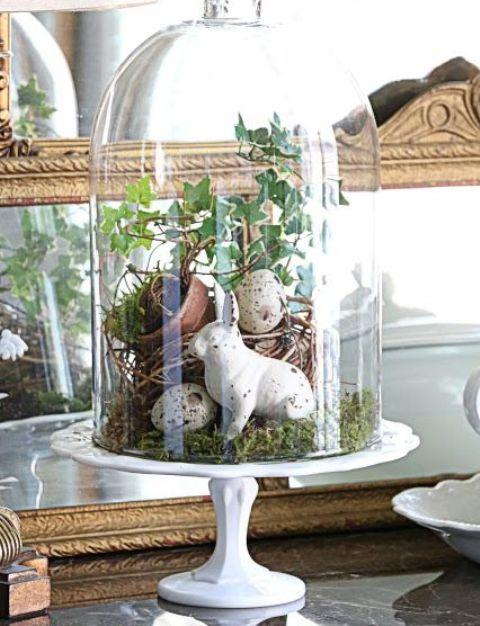 a cloche with speckled eggs, greenery, moss and a bunny