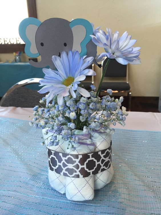 a diaper centerpiece with blue flowers and a paper elephant