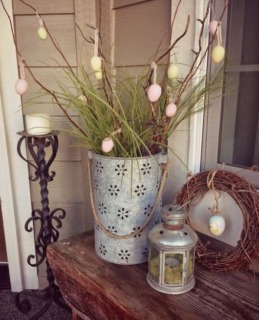 a perforated bucket with branches and grass, egg ornaments