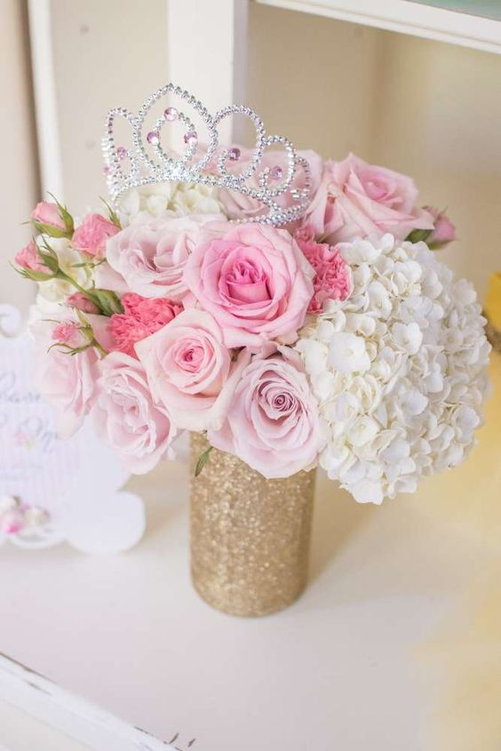 a glitter vase with pink and white florals and a tiara