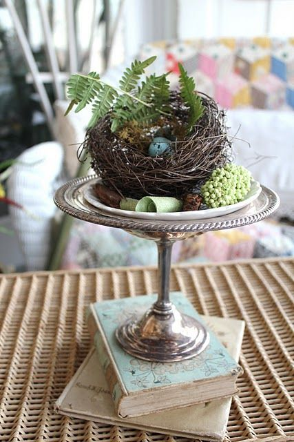 a silver stand with a grapevine nest, fern and a blue egg