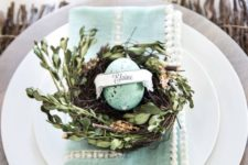 08 a wooden platter, a mint pompom napkin and a nest with greenery and a speckled mint egg card holder