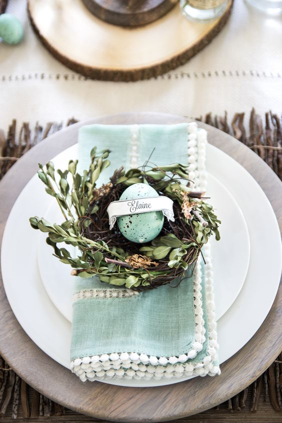 a wooden platter, a mint pompom napkin and a nest with greenery and a speckled mint egg card holder