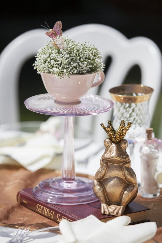 a pink cup with baby's breath and a butterfly on a glass stand