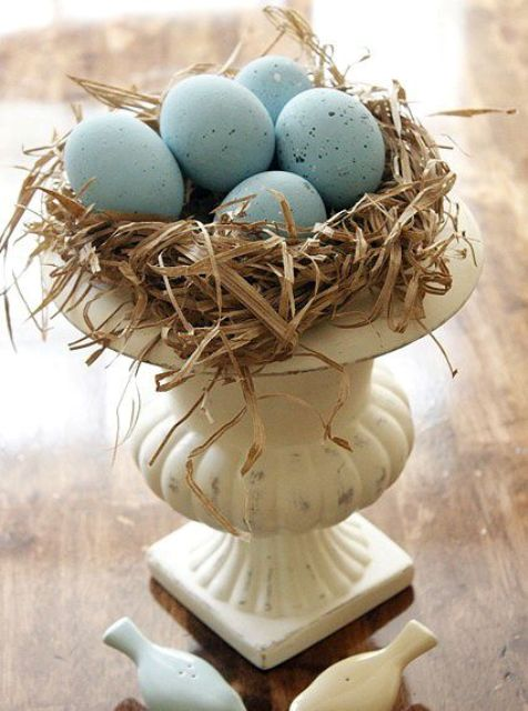 a vintage urn with hay ad blue speckled eggs