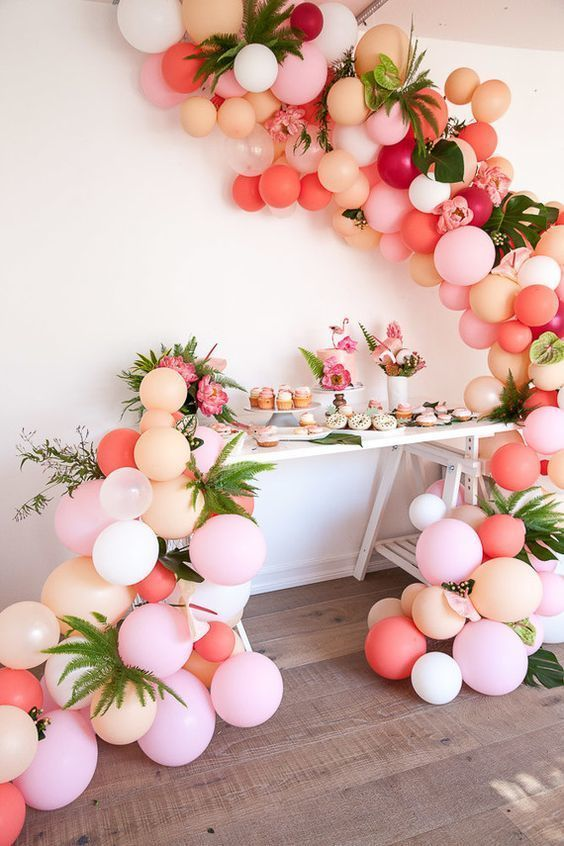 blush, peach and pink balloon garlands with palm leaves for a tropical celebration