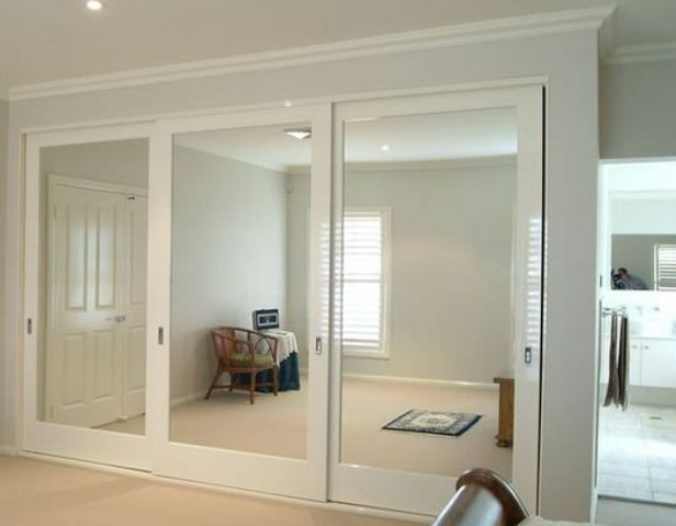 whole wall of sliding mirror closet doors visually doubles the space