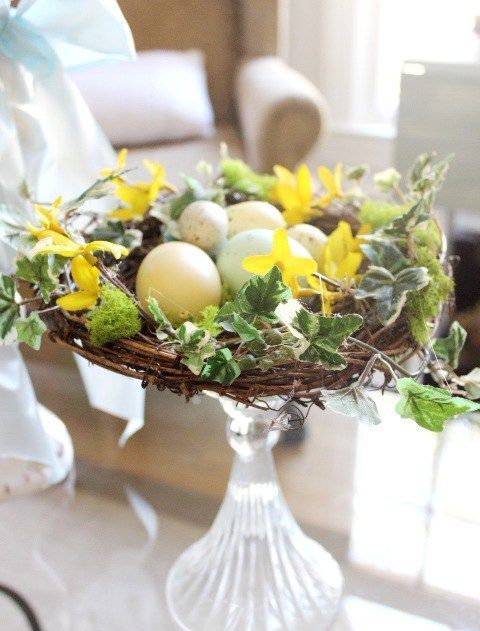 a glass stand with a nest, faux leaves and speckled eggs