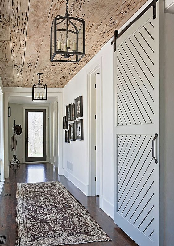 a sliding barn door and pecky cypress ceiling turn an ordinary side hallway into a stunning entrance