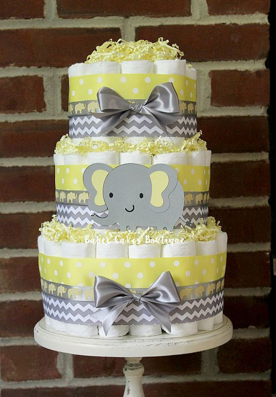 yellow and grey disaper cake with ribbon bows and an elephant
