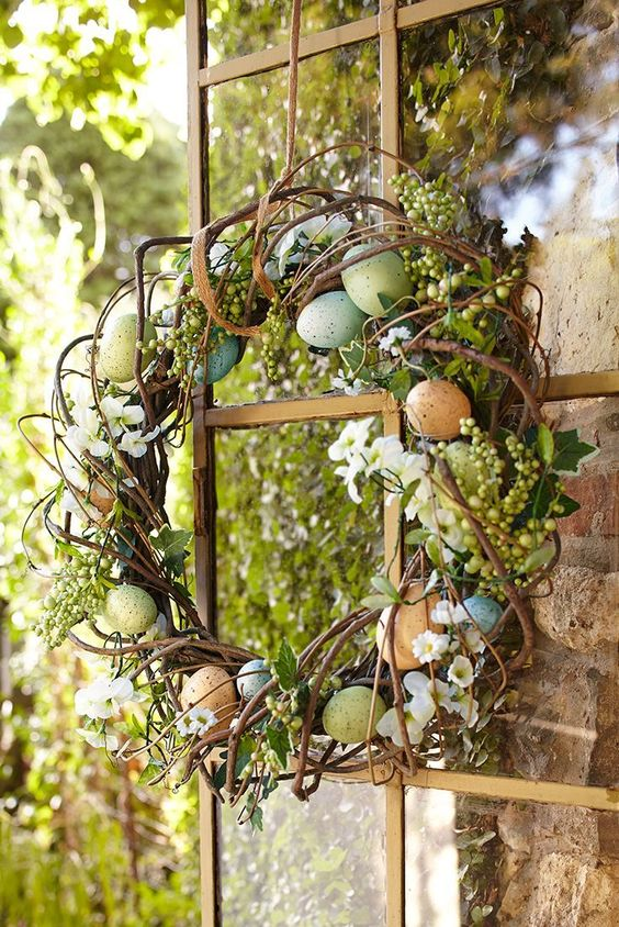 an arrangement of faux speckled eggs, ivy and a combination of white floral blooms