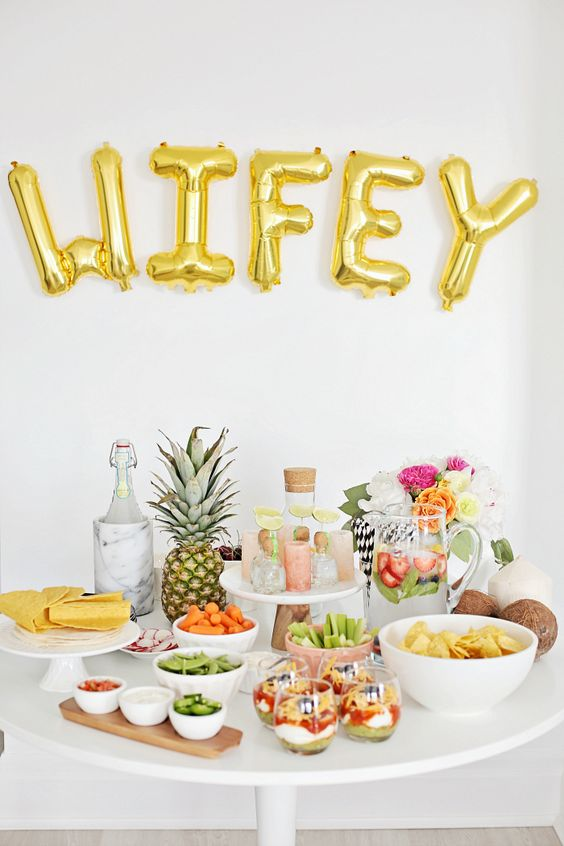 gold WIFEY balloons as a fruit table backdrop
