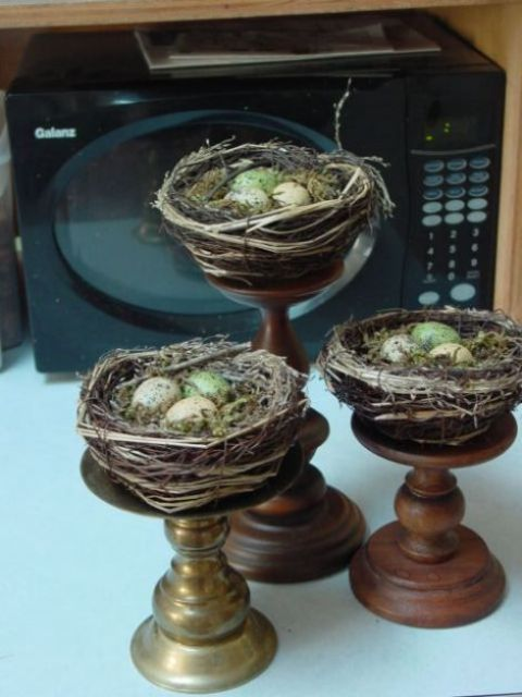 grapevine bird nests with speckled eggs on vintage wooden and metal stands