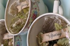 11 vintage cups with hay, speckled eggs, lace and paper