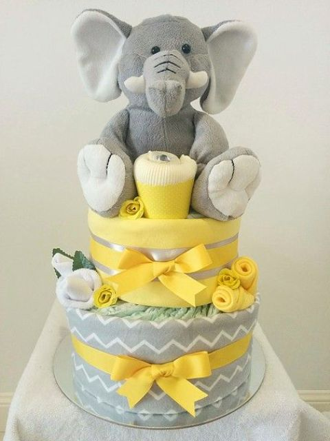 yellow and grey nappies cake with a stuffed elephant on top