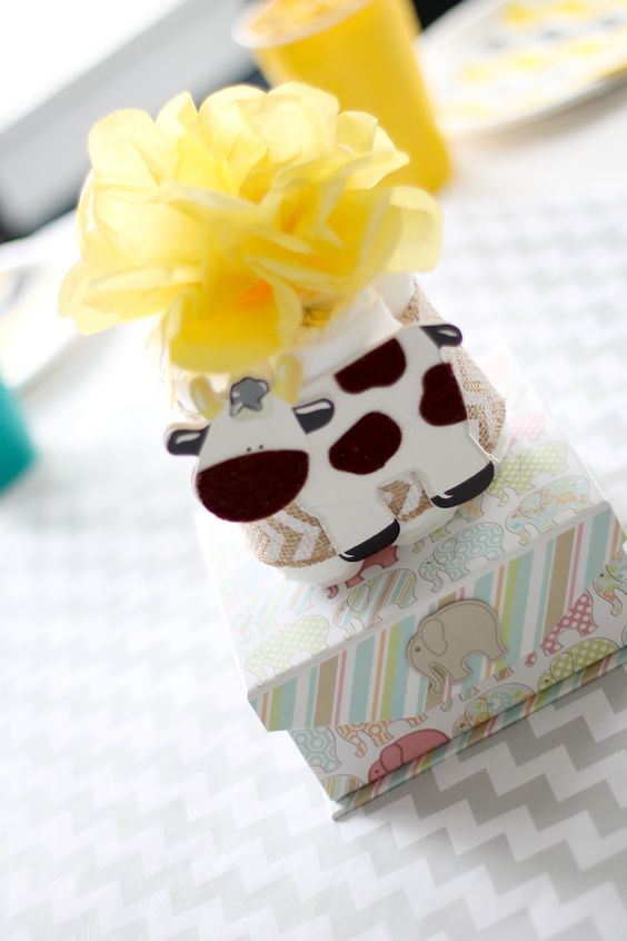 a box with diapers and a cow plus a fluffy yellow pompom