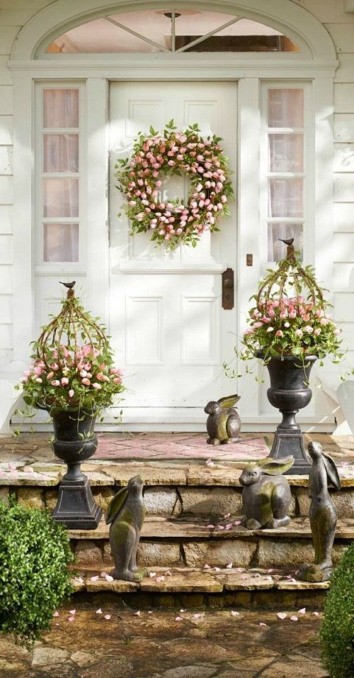 a lush flower wreath and some porch decorations