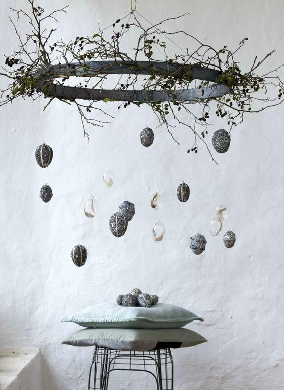 a modern installation with branches and twine and transparent eggs