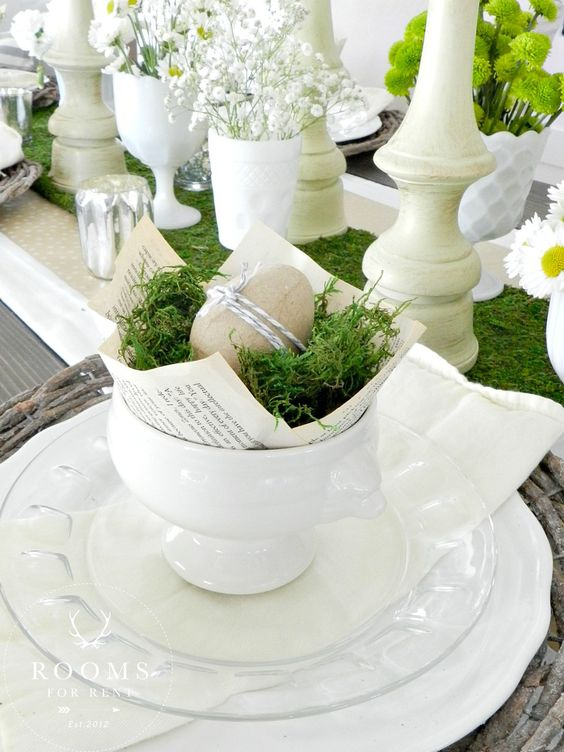 clear white plates, a bowl with moss and paper mache eggs