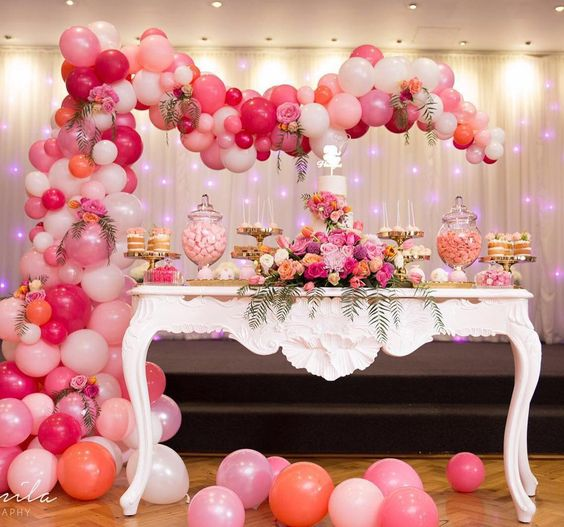 pink, blush and white balloon arch over the dessert table