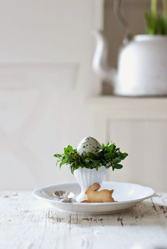 a place setting with a bunny cookie, a speckled egg and greenery