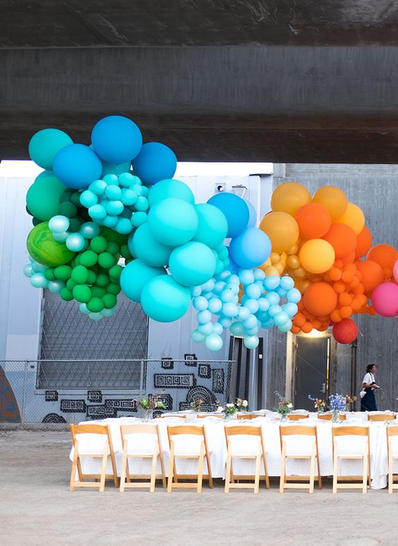 oversized rainbow balloon installation over the table