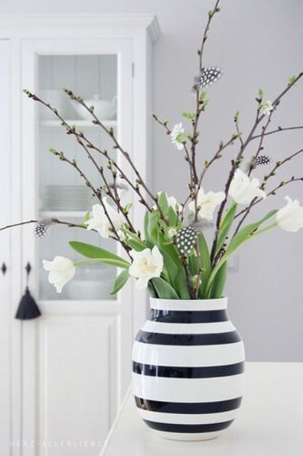 a striped monochrome vase with white tulips and willow