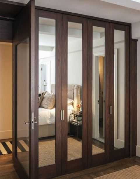 dark stained wood mirror wardrobe doors aren't excessive but still make the space look bigger