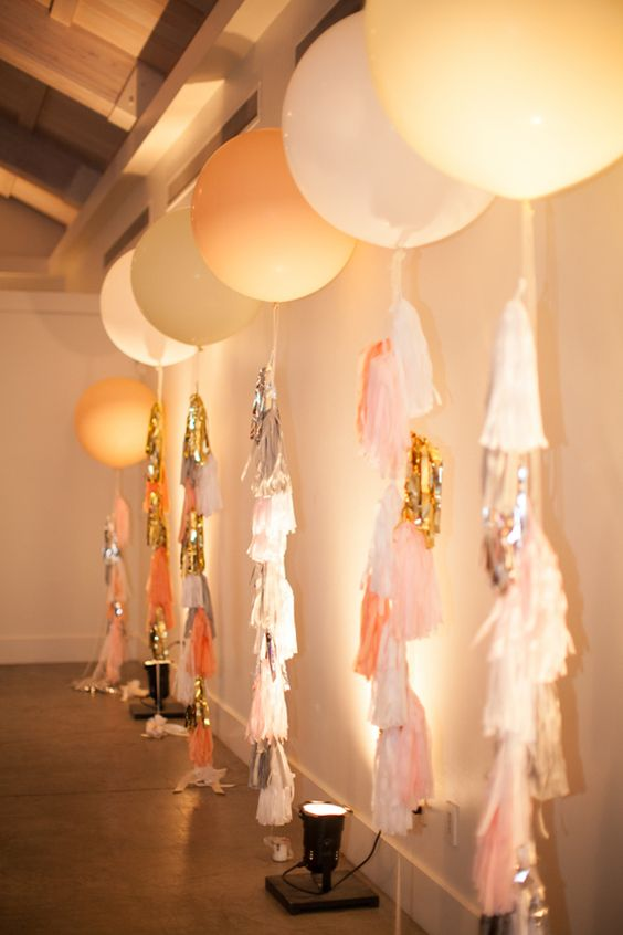14 giant balloons with tassels at the lit up walls