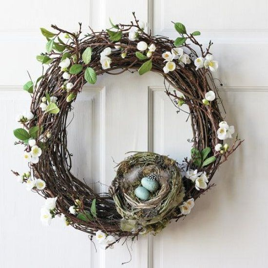 grapevine spring wreath with faux flowers and leaves, a nest with feathers and eggs
