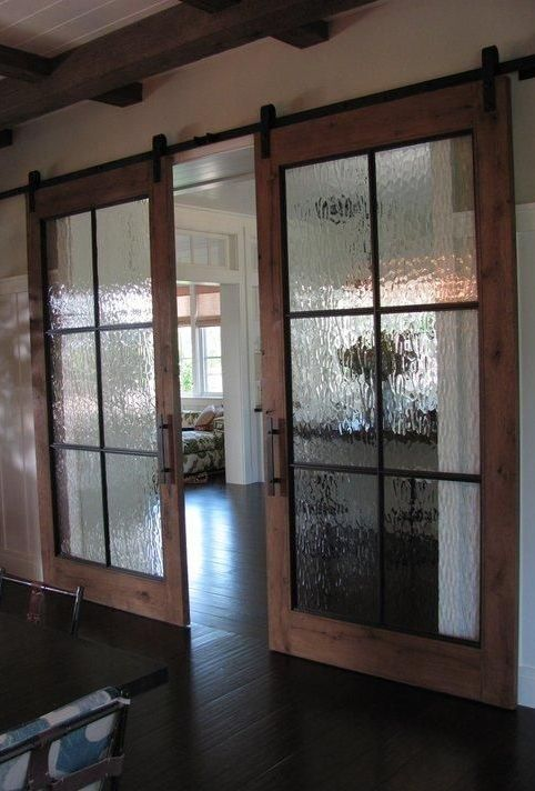 wooden barn doors with rian glass and framing for more privacy