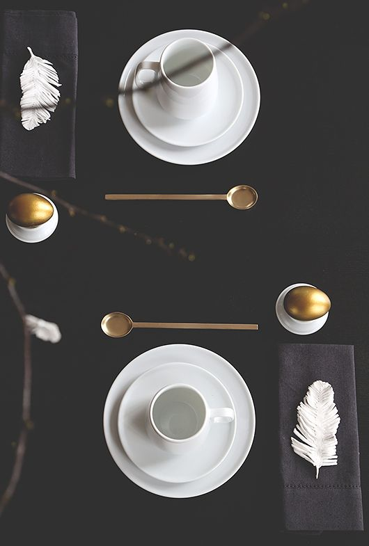 black tablecloth, gilded tableware and eggs and white dishes and feathers