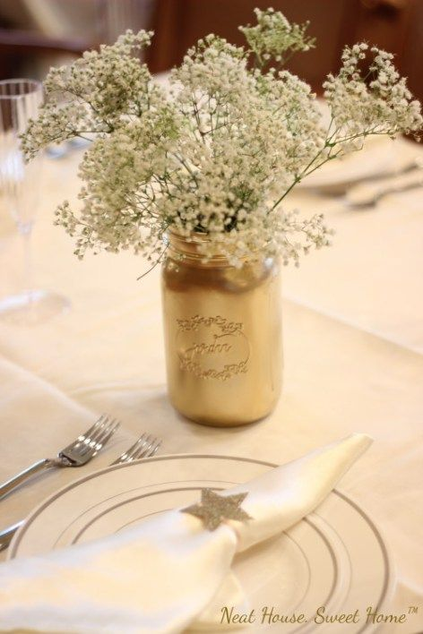 a gold mason jar with baby's breath for a gender neutral shower