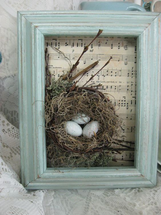 a mint colored frame with note ppaer and a small bird nest with twigs and speckled eggs