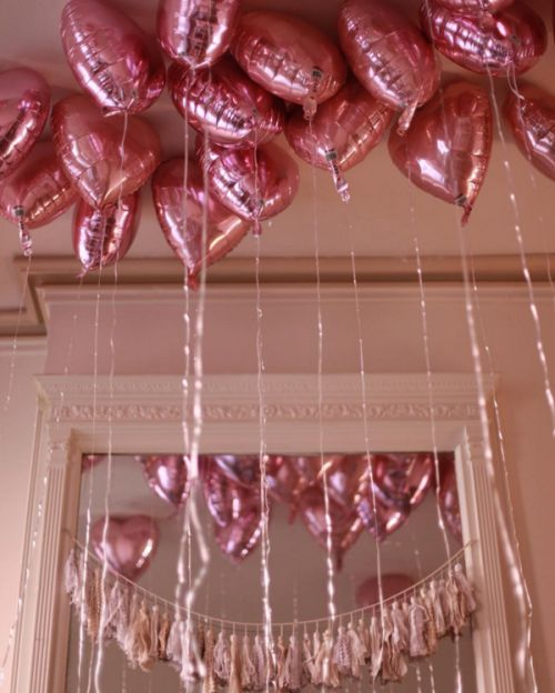 metallic pink heart-shaped balloons floating over the whole party