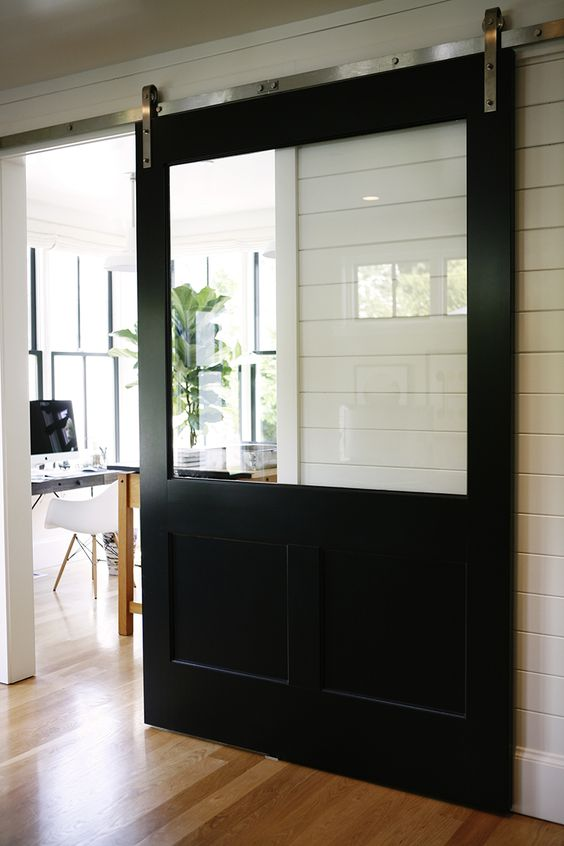 oversized black barn door with a glass top makes a statement