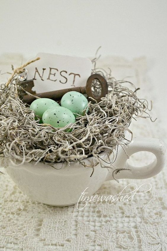 a nest in a cup with a vintage key, hay and speckled eggs