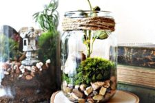 17 a small jar terrarium with rocks, moss and flowers, a wooden slice as a stand