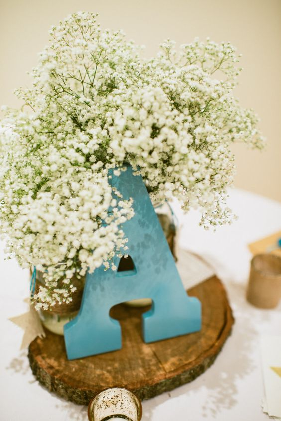 a wood slice with baby's breath and a turquoise letter