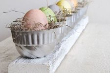17 a wooden board, metal cups with straw and pastel-colored eggs